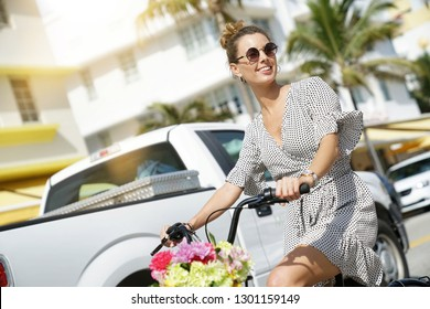 Stunning summery young woman on cute bicycle in art deco city