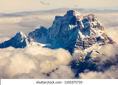 Stunning sunny winter view to peaks in moutains and clouds in Dolomites Alps, Italy