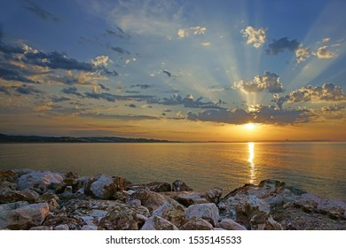 A stunning sunrise with crepuscular rays over the Bay of Lagos looking towards Portimao, Lagos, The Algarve, Portugal