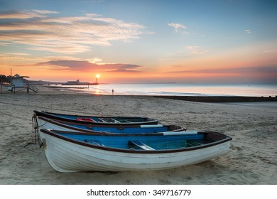 Stunning sunrise over fishing boats at Durley Chine on Bournemouth beach in Dorset with the sun rising over the end of the pier