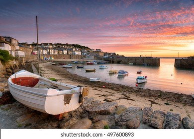 Stunning sunrise over fishing boats at Mousehole near Penzance in Cornwall