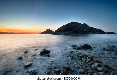 Stunning sunrise over The Mumbles lighthouse in Swansea Bay on the south coast of Wales