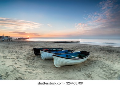 Stunning sunrise over a row of fishing boats on Bournemouth beach in Dorset, with the pier in the far distance