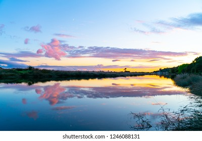Stunning sunrise and reflection on calm arm leading to Ruataniwha Inlet Collingwood, South Island New Zealand