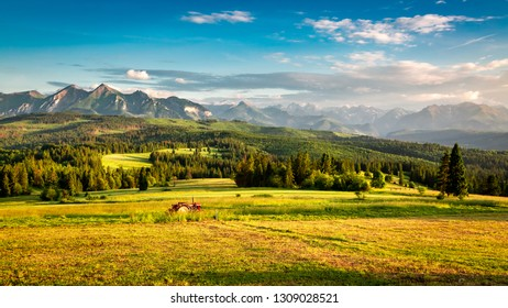 Stunning sunset at Belianske Tatra mountains with tractor, Poland