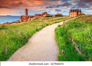 Stunning sunset with lighthouse of Ploumanach Mean Ruz in Perros-Guirec on Pink Granite Coast, Brittany, France, Europe