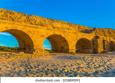 Stunning sunset on the Mediterranean coast in Israel. Well-preserved aqueduct, built in Caesarea at the beginning of the Byzantine period. Concept of active, ecological and historical tourism