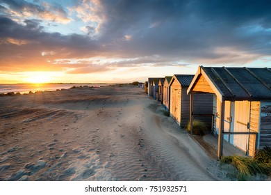 Stunning sunset over beach huts at West Wittering on the Sussex coastline