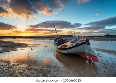 Stunning sunset over a fishing boat at Burnham Overy Staithe on the Norfolk Coast