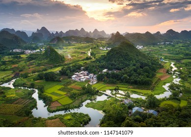 Stunning sunset over karst formations and rice fields landscape near Yangshuo in Guangxi province of China