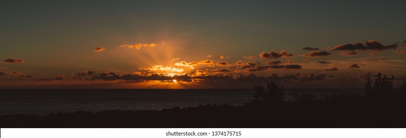 Stunning sunset panoramic scenery with an amazing cloudscape over the sea; evening cloudscape lit by the sun with the coastline in the foreground and seascape with sun rays through clouds behind