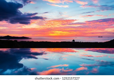 Stunning sunset reflected in the smooth water of a pool overlooing the popular vacation destination of Playa Flamingo, Costa Rica