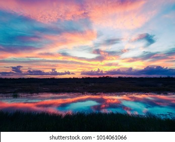 stunning sunset reflects into a river in the swamp