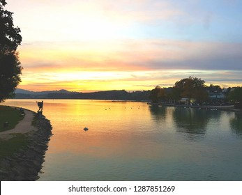 Stunning sunset scenery over a lake in Austria with the silhouette of a statue of a gondolier on the shore