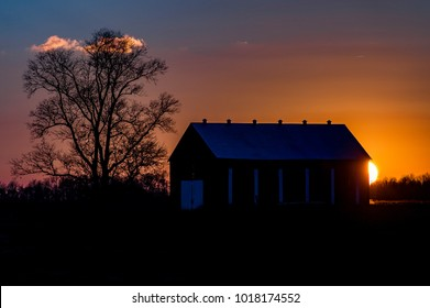 A stunning sunset view of a traditional tobacco barn on a farm in central Kentucky.