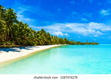 Stunning tropical Aitutaki island with palm trees, white sand, turquoise ocean water and blue sky at Cook Islands, South Pacific. Copy space for text
