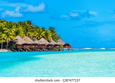 Stunning tropical Aitutaki island with palm trees, white sand, turquoise ocean water and blue sky at Cook Islands, South Pacific. Water bungalow