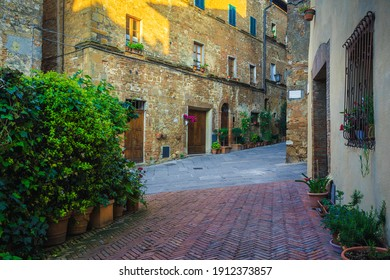 Stunning tuscan street view. Fantastic medieval brick houses and paved street. Decorated entrances with colorful flowers and green plants, Tuscany, Italy, Europe