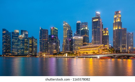 Stunning twilight view of Singapore city cityscape skyscrapers day to night transition timelapse, Jubilee Bridge, Merlion waterfront, modern financial and business buildings at Marina Bay attraction