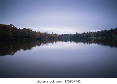 Stunning vibrant Autumn woodland reflected in still lake water during twilight landscape