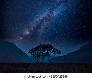 Stunning vibrant Milky Way composite image over landscape of countryside surrounding crummock water in lake district in england