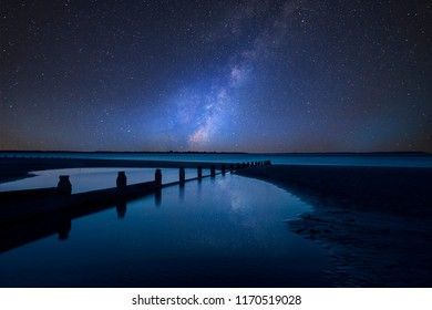 Stunning vibrant Milky Way composite image over landscape of Beautiful long exposure beach