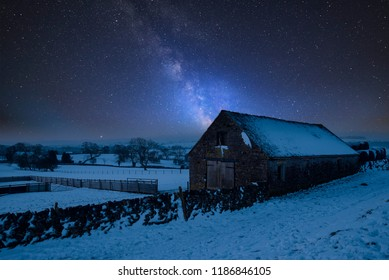 Stunning vibrant Milky Way composite image over landscape of Snow covered barn in Peak District in England