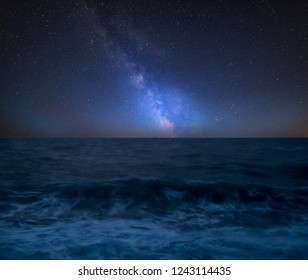 Stunning vibrant Milky Way composite image over landscape of Waves breaking onto beach