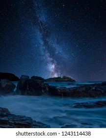 Stunning vibrant Milky Way composite image over landscape of Godrevy lighthouse on Cornwall coastline in England