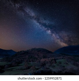 Stunning vibrant Milky Way composite image over Catbells landscape near Derwentwater in the Lake District with vibrant Fall colors all around the contryside vista