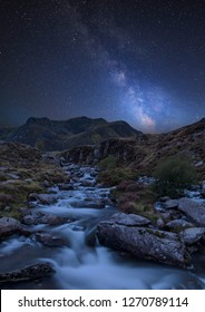 Stunning vibrant Milky Way composite image over Landscape image of river flowing down mountain range near Llyn Ogwen and Llyn Idwal in Snowdonia