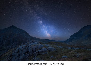 Stunning vibrant Milky Way composite image over Beautiful moody landscape image of Nant Francon valley in Snowdonia