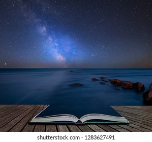 Stunning vibrant Milky Way composite image over landscape of Beautfiul long exposure of sea over rocks coming out of pages of open story book