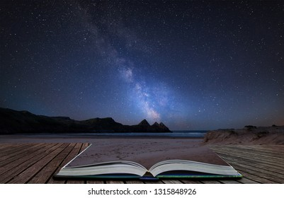 Stunning vibrant Milky Way composite image over landscape of yellow sandy beach Three Cliffs bay coming out of pages in magical story book