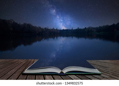 Stunning vibrant Milky Way composite image over landscape of still lake coming out of pages in magical story book