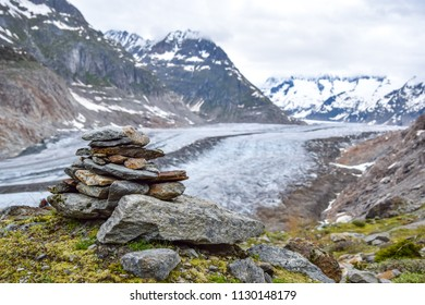 Stunning view of Aletsch glacier, the largest glacier in the European Alps, located in the Bernese Alps in Switzerland. A Stoneman (rock cairn) in the foreground. Selective focus.