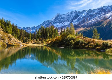 Stunning view of the Alps with reflection in beautiful pond on the hiking path above Loetschental, on a sunny autumn day in canton of Valais, Switzerland.