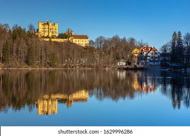 Stunning view of the Alpsee lake in winter on a sunny day with the Hohenschwangau Castle and Bavaria Alps in background, with beautiful reflections in water, Schwangau, Bavaria, Germany