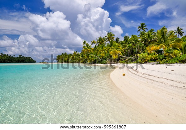 Stunning view of a beach on One Foot Island, also called Tapuaetai, in the lagoon of Aitutaki, Cook Islands, in the South Pacific Ocean. Clear water, palm trees and white sand beach on a sunny day.