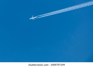 Stunning view of a commercial airplane forming contrails on a blue sky.