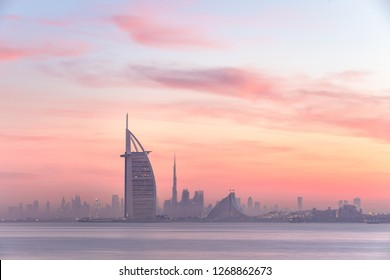 Stunning view of Dubai skyline from Jumeirah beach to Downtown lighted with warm pastel sunrise colors. Dubai, UAE.
