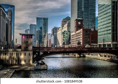 Stunning view, facing north-west, of the Chicago river, Dearborn Street bridge and surrounding buildings on an partly cloudy day in March. Light casts a beautiful glow on structures and water.