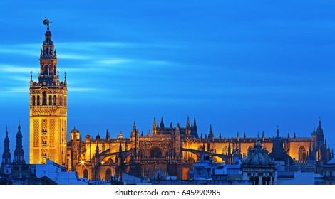 Stunning view of Giralda and Cathedral of Seville illuminated at blue hour