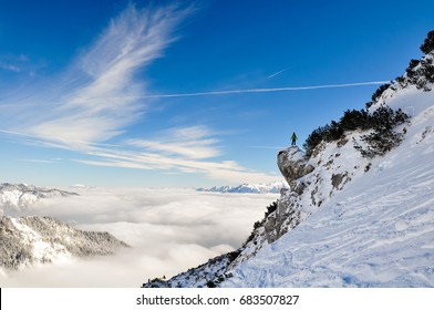 Stunning view of a hiker standing on a steep cliff near the Bavarian town of Garmisch Partenkirchen near Zugspitze mountain in Germany. Beautiful snow landscape in winter. Deep snow off piste slope.