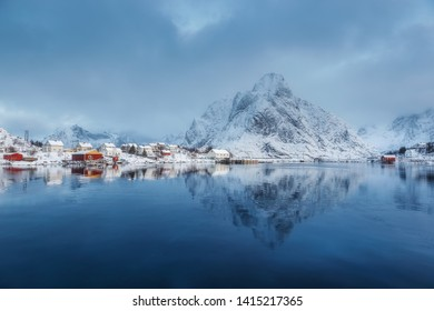 Stunning view of the mountain reflected in the water. Early blue morning in a Norwegian village. Gentle winter sunrise on Lofoten. Beauty of snowy winter nature concept background. Norway. Lofoten.