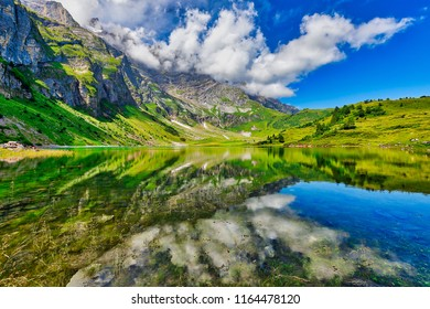 Stunning view of Oberlegisee lake with beautiful reflections on a sunny summer day, in Braunwald, Canton of Glarus, Switzerland