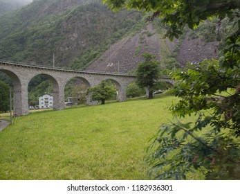 Stunning view of old arch bridge in Italian Alps surrounded with green trees, field and mountains