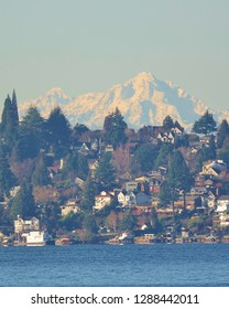 Stunning view on clear winter Pacific Northwest day from Kirkland, WA looking across blue water of Lake Washington at a lakeside Seattle neighborhood with snow covered Olympic Mountains as a backdrop.