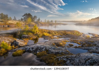 Stunning view of the rocks covered with yellow moss and sun-drenched islands. Beauty of summer nature concept background. Foggy and sunny landscape. Ladoga lake.Archipelago.National Park of Karelia.