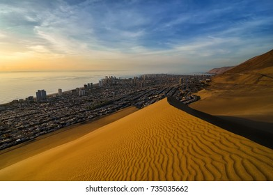 Stunning view to sand dunes, ocean and Iquique city at sunset